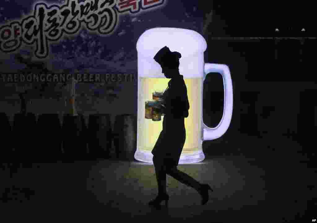 អ្នកបម្រើស្រីម្នាក់ចាំងស្រមោលរបស់ខ្លួនទៅនឹងផ្ទាំងផ្សាយពាណិជ្ជកម្មមួយ នៅពេលនាងកាន់កែវស្រាបៀរក្នុងពិធី Taedonggang Beer នៅក្នុងក្រុងព្យុងយ៉ាង ប្រទេសកូរ៉េខាងជើង។