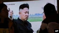 지난달 27일 한국 서울역에서 시민들이 북한 간부 총살에 관한 TV 뉴스를 시청하고 있는 가운데 김정은 북한 국무위원장의 자료사진이 나오고 있다.