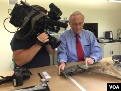 Joe Reynolds, CEO of RTI Group LLC. examines structural plane parts for thermal damage, Aug. 11, 2015. (Photo: Carolyn Presutti / VOA)