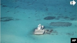 In this photo taken Feb. 28, 2013 by a surveillance plane, and released Thursday, May 15, 2014, by the Philippine Department of Foreign Affairs, Chinese-made structures stands on the Johnson Reef, called Mabini by the Philippines and Chigua by China, in the Spratly Islands in South China Sea.