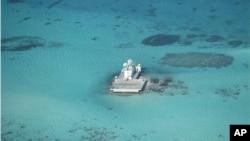 FILE - In this photo taken Feb. 28, 2013 by a surveillance plane, and released on May 15, 2014, by the Philippine Department of Foreign Affairs, Chinese-made structures stands on the Johnson Reef, called Mabini by the Philippines and Chigua by China, in the Spratly Islands in South China Sea.