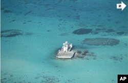 In this photo taken Feb. 28, 2013 by a surveillance plane, and released Thursday, May 15, 2014, by the Philippine Department of Foreign Affairs, Chinese-made structures stands on the Johnson Reef, called Mabini by the Philippines and Chigua by China, in t