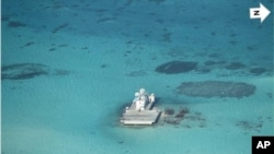 In this photo taken Feb. 28, 2013 by a surveillance plane, and released Thursday, May 15, 2014, by the Philippine Department of Foreign Affairs, Chinese-made structures stands on the Johnson Reef.