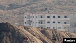 Sebuah bendera ISIS dapat kelihatan di sebuah gedung Kobani dari seberang perbatasan di Turki Senin (6/10).