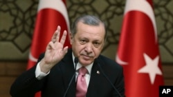 "Turkey's President Recep Tayyip Erdogan gestures as he addresses local administrators, in Ankara, Turkey, Wednesday, Feb. 8, 2017. In a sign of ameliorating ties, Turkish officials said Wednesday that U.S. President Donald Trump looked ""positively"" on two"