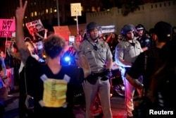 Police are surrounded by demonstrators who took over the Hollywood 101 Freeway just north of Los Angeles City Hall in protest to the election of Republican Donald Trump as President of the United States in Los Angeles, California, Nov. 9, 2016.