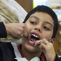 A young man in Nebraska tries his hand at flossing in this file photo.
