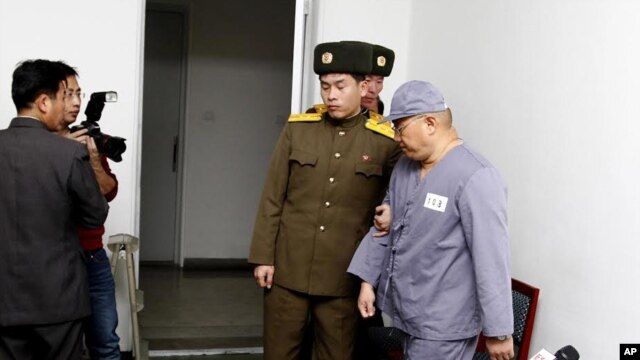 American missionary Kenneth Bae, right, leaves after speaking to reporters at Pyongyang Friendship Hospital in Pyongyang Monday, Jan. 20, 2014.