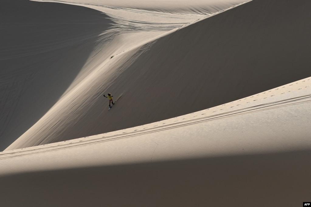 Нгуен Тай Бинь бороздит песчаные дюны на своем сноуборде в Южном вьетнамском городе Муйне.