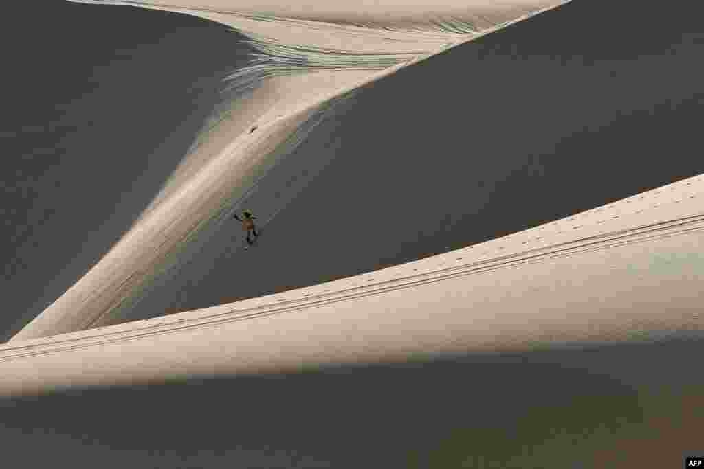 Nguyen Thai Binh rides down sand dunes on his snowboard in the southern Vietnamese town of Mui Ne.