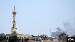 Columnas de humo emergen del complejo Bab Al-Aziziya de Gadhafi, cuando los rebeldes lanzan un fuerte ataque.