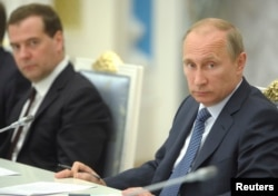 FILE - Russian President Vladimir Putin, right, chairs a meeting on economic and social issues, as Prime Minister Dmitry Medvedev sits nearby, in Moscow, May 7, 2014. Memorial board member Yan Rachinsky says the Russian leaders don't understand that their system of values is helping to revive Stalinism.