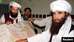 Jalaluddin Haqqani (R), the leader of the Haqqani network, points to a map of Afghanistan during a visit to Pakistan while his son looks on in this October 19, 2001 photograph.