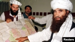 Jalaluddin Haqqani (R), the Taliban's Minister for Tribal Affairs, points to a map of Afghanistan during a visit to Islamabad, Pakistan while his son Naziruddin (L) looks on in this October 19, 2001 file photograph.
