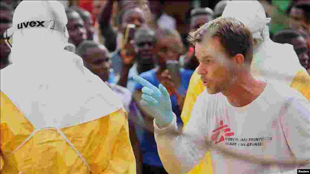 A doctor speaks as health workers surround an Ebola patient who escaped from quarantine from the Elwa Hospital, Paynesville, Liberia, Sept. 1, 2014.