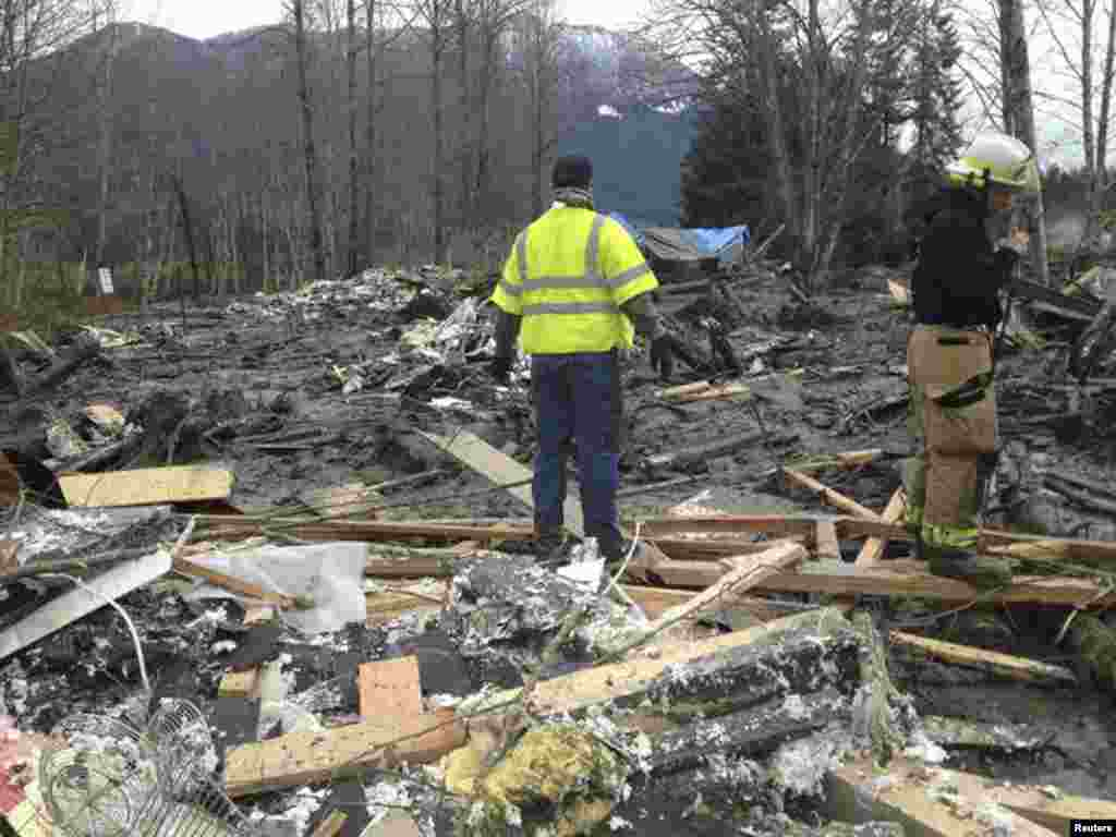 Officials survey a large mudslide that pushed debris and at least one house onto Highway 530 near Oso, Washington, March 22, 2014.