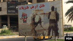 FILE - A poster on a Baghdad street calls for volunteers to join the Hashd al-Shaabi militia, May 18, 2016. Iran might bring this and other Shiite militias in to fight threats to the Tehran government, an Iranian official says. (S. Behn/VOA)