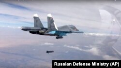 FILE - A bomb is released from Russian Su-34 strike fighter in Syria, Oct. 9, 2015.