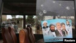 Một tấm poster vận động bầu cử của ứng viên tổng thống Afghanistan Abdullah Abdullah trên tấm gương của một xe buýt bị hỏng sau vụ đánh bom.