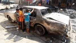 Iraqi children inspect a burned out car at the site of a car bomb attack that exploded the previous day in a commercial street of Baghdad's eastern neighborhood of Mashtal, Sept.16, 2013.