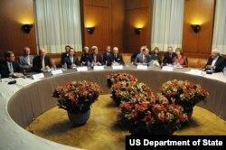 Ngoại trưởng John Kerry ngồi cùng với các ngoại trưởng của nhóm P5+1 cũng như Đại diện Cấp cao Liên hiệp châu Âu Catherine Ashton và Ngoại trưởng Iran Javad Zarif, (ngoài cùng bên phải.)