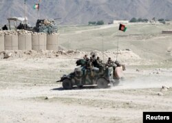 FILE - Afghan special forces patrol in Pandola village near the site of a U.S. bombing in the Achin district of Nangarhar province in eastern Afghanistan, April 14, 2017.