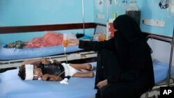 FILE - A mother holds up a feeding tube for her malnourished son at a feeding center in a hospital in Hodeida, Yemen, Sept. 27, 2018.