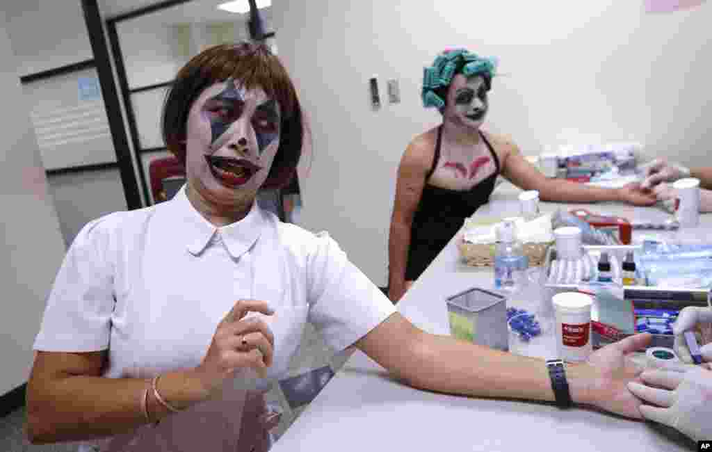 Manful Bumroongton, front, and Thanat Chotrat dressed in a ghost costume for Halloween take blood test before donating blood at the Thai Red Cross in Bangkok, Thailand.