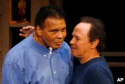FILE - Comedian Billy Crystal, right, hugs boxing legend Muhammad Ali on his 65th birthday on the campus of Arizona State University in Tempe, Ariz., Jan. 17, 2007. Crystal is expected to speak at Ali's funeral in Louisville, Ky., June 10, 2016.