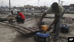 FILE - Due to Nigeria's decrepit national power grid, a man refuels a small generator in central Lagos, Nigeria, August 2010.
