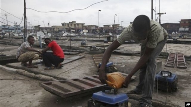 Due to Nigeria's decrepit national power grid, a man refuels a small generator in central Lagos, August 2010.