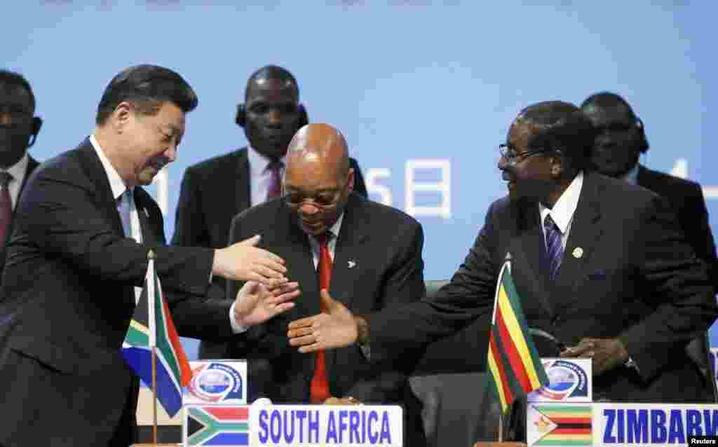 Rais Xi Jinping wa China (kushoto) akisalimiana na Rais Robert Mugabe wa Zimbabwe huku Rais Jacob Zuma wa Afrika Kusini akitizama wakati wa Mkutano wa viongozi wa Afrika na China, huko Sandton, Johannesburg, December 4, 2015.