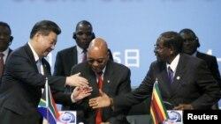 2015年12月4日,中国国家主席习近平在南非约翰内斯堡参加中非合作论坛。图为习近平与津巴布韦总统穆加贝(右边)握手。中间是南非总统祖马。(资料照片)
