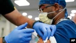 Seorang petugas kesehatan menerima suntikan booster vaksin COVID-19 Pfizer di Jackson Memorial Hospital in Miami pada 5 Oktober 2021. (Foto: AP/Lynne Sladky)