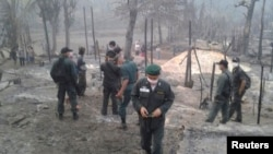 Thai security force inspect the site of fire at the Ban Mae Surin refugee camp near Mae Hong Son, 800 km (497 miles) north of Bangkok, March 23, 2013.