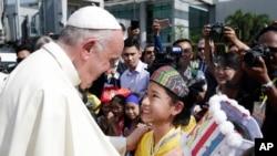 Paus Fransiskus disambut warga setempat setibanya di bandara Internasional Yangon, Myanmar 27 November 2017.
