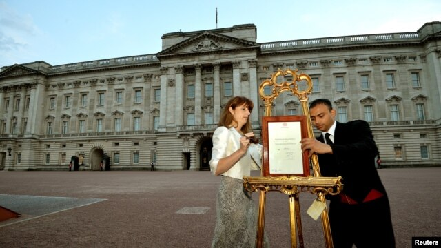 The press Secretary to Britain's Queen Elizabeth and footman Badar Azim place a notice announcing Prince George's birth.