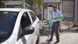 FILE - A driver of an electric car charges his vehicle at public charging station in New Delhi, India, April 1, 2021.