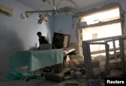 FILE - A medic inspects the damage inside Anadan Hospital, sponsored by Union of Medical Care and Relief Organizations (UOSSM), after it was hit by an airstrike in the rebel-held city of Anadan, northern Aleppo province, Syria, July 31, 2016.