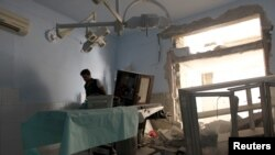 FILE - A medic inspects the damage inside Anadan Hospital, sponsored by Union of Medical Care and Relief Organizations, after it was hit by an airstrike in the rebel-held city of Anadan, northern Aleppo province, Syria, July 31, 2016.