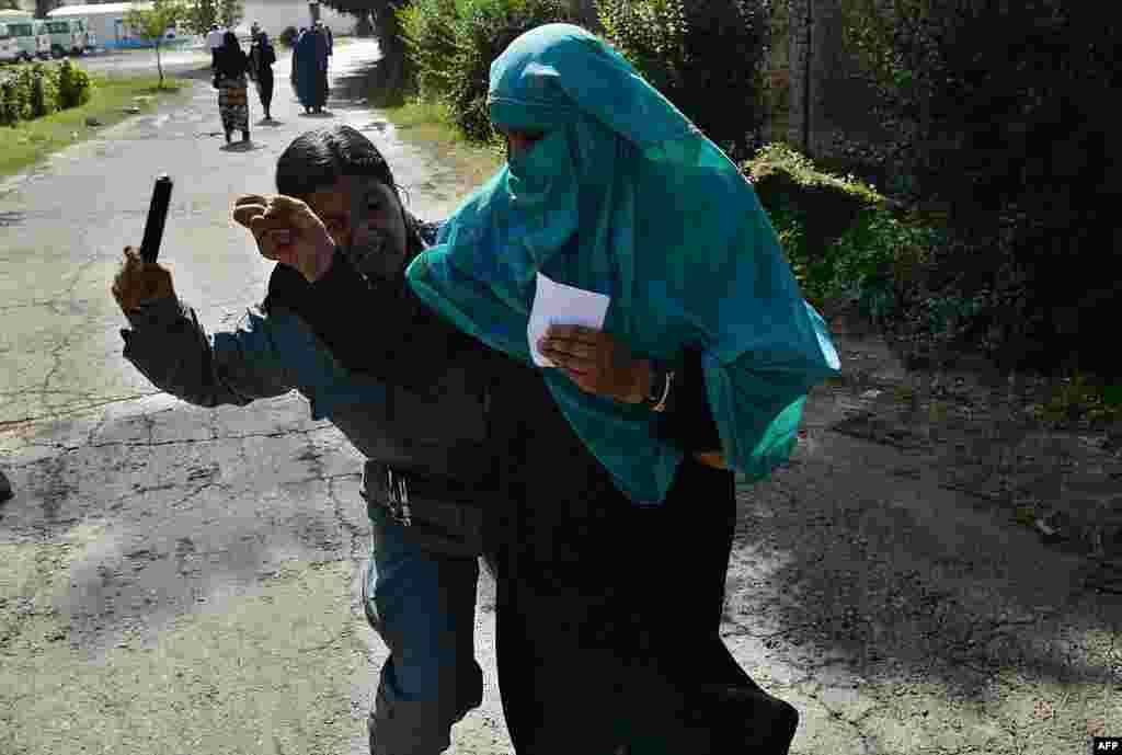 Snimljeno u Kabulu: Afganistanka, policajka, tuče drugu Afganistanku koja je čekala da joj bude udijeljeno, poklonjeno nešto hrane.