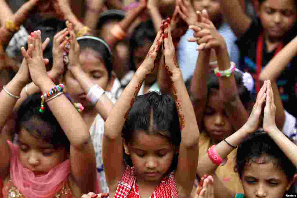 Schoolchildren offer prayers to pay tribute to the victims of the Bastille Day truck attack in Nice, at a school in Ahmedabad, India.