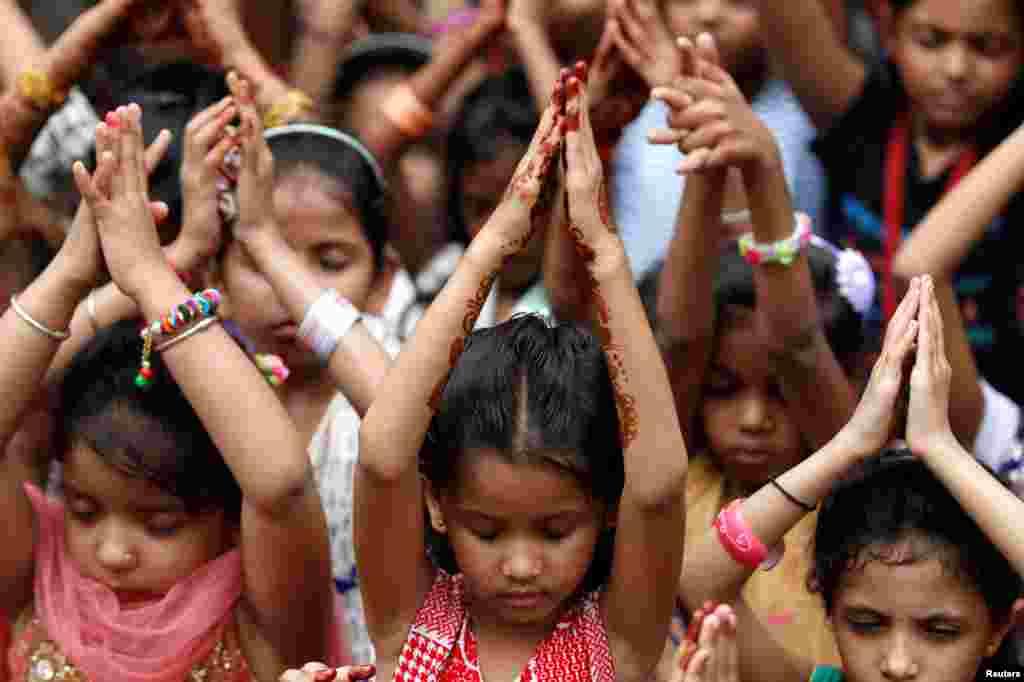Học sinh cầu nguyện để tưởng niệm những nạn nhân trong vụ tấn công xe tải trong Ngày Bastille ở Nice, tại một trường học ở thành phố Ahmedabad, Ấn Độ.