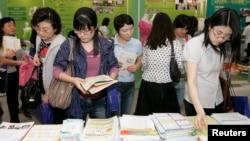 한국 서울에서 열린 여성 취업박람회에서 구직자들이 직업 훈련 센터에서 제공하는 유인물을 들여다보고 있다. (자료사진)