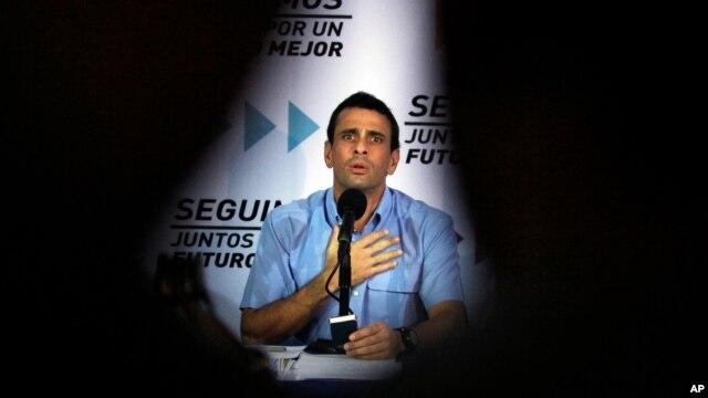 El líder de la oposición venezolana Henrique Capriles es flanqueado por las siluetas de los periodistas.