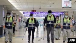戴着口罩的工作人员在台北桃园机场喷洒消毒药水防范新冠病毒。(2020年1月22日)