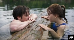 """This image released by Apple TV+ shows Ferdia Walsh-Peelo, left, and Emilia Jones in a scene from """"CODA."""" (Apple TV+ via AP)"""