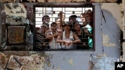 Para narapidana mengintip dari balik gedung LP Tanjung Gusta di Medan (12/7) yang rusak dibakar. (AP/Binsar Bakkara)