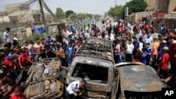 Warga berkumpul di lokasi ledakan bom mobil di distrik Sadr City, Baghdad, Kamis (16/5).