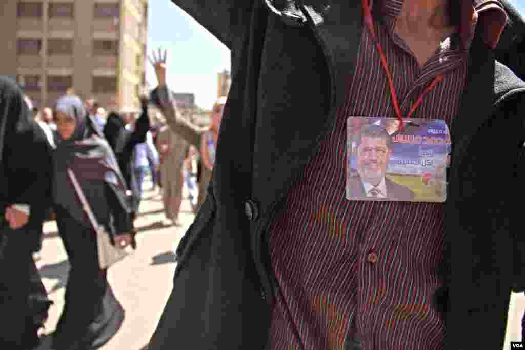 A protester wears an image of ousted President Mohamed Morsi during a demonstration in Cairo, March 28, 2014. (Hamada Elrassam/VOA)